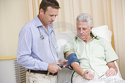 Doctor checking man s blood pressure
