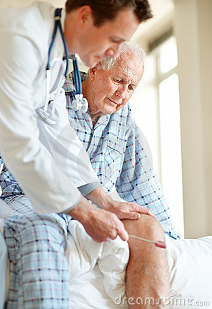 Doctor checking old man knee using a reflex hammer