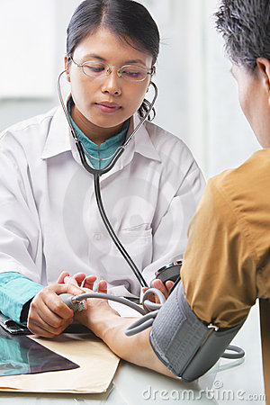 Doctor checking patient blood pressure