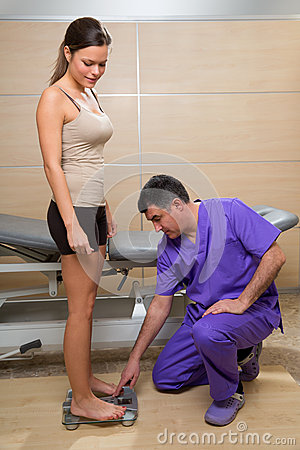 Doctor checking weight scale measure of woman patient