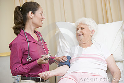 Doctor checking woman s blood pressure