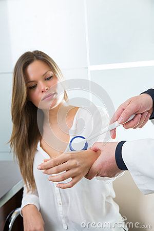 Doctor checking wrist with reflex round hammer to woman