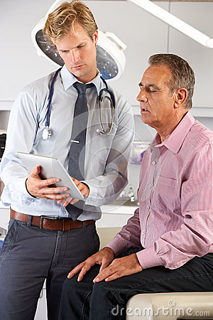 Doctor Discussing Records With Patient Using Digital Tablet
