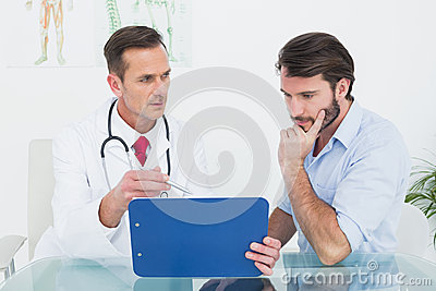 Doctor discussing reports with patient at medical office