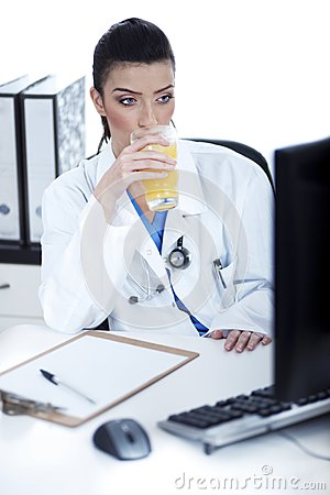Doctor drinking a glass of juice at her workplace