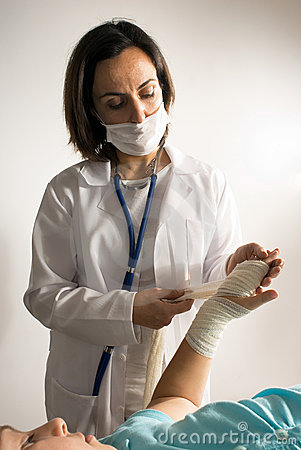 Doctor Examines a Bandaged Arm