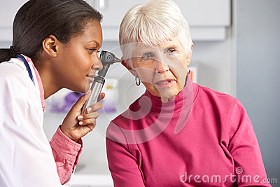 Doctor Examining Senior Female Patient s Ears