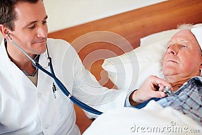 Doctor examining a senior man's heart beat