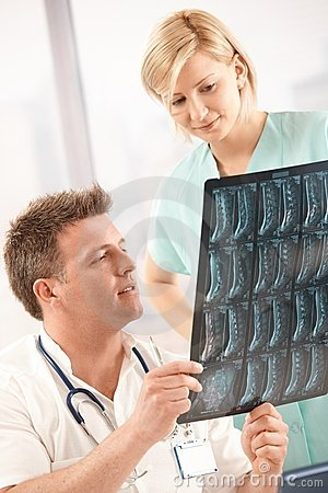 Doctor examining x-ray image with nurse