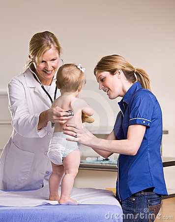 Doctor giving baby girl checkup in doctor office
