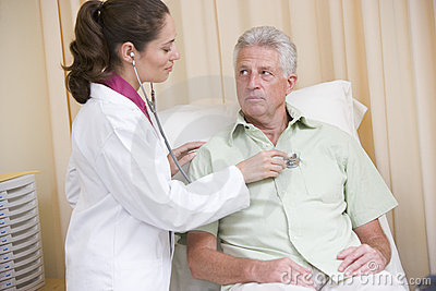 Doctor giving checkup with stethoscope to man