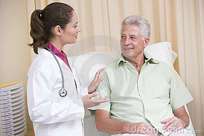 Doctor giving checkup to man in exam room