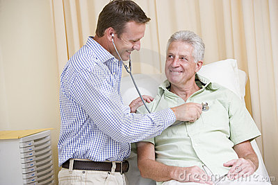 Doctor giving man checkup with stethoscope in exam