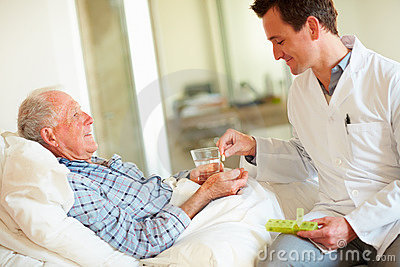 Doctor giving an old man a pill while at his bed