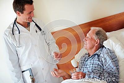 Doctor giving pills to an elderly man