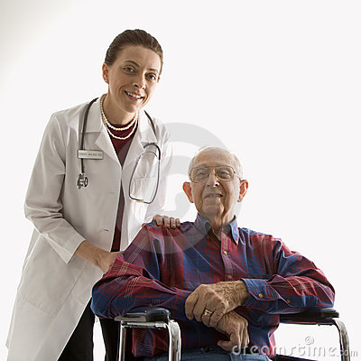 Doctor with hands on elderly man s shoulder in wheelchair.