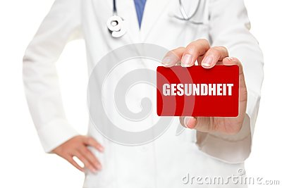 Doctor holding GESUNDHEIT card in german