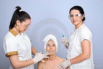 Doctor inject botox to senior cheek woman