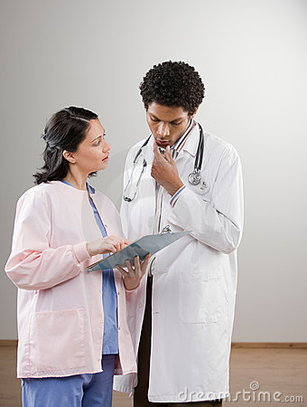 Doctor in lab coat listening to nurse