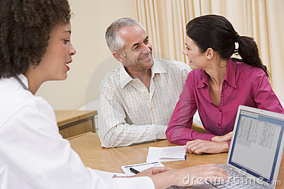 Doctor with laptop and couple in doctor s office