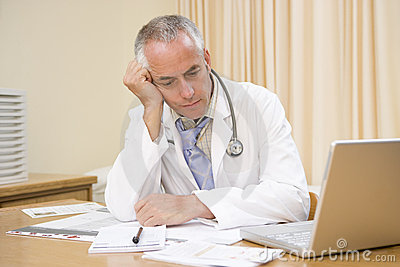 Doctor with laptop in doctor s office