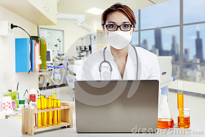 Doctor with laptop and flasks looking at camera