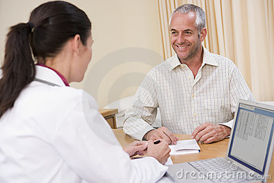 Doctor with laptop and man in doctor s office