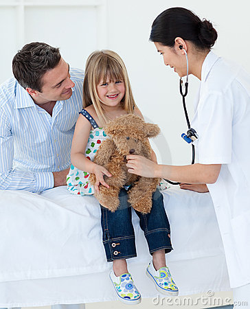 Doctor and little girl examining a teddy bear