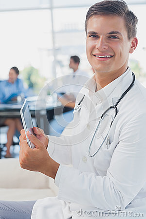 Doctor looking at the camera and using tablet pc