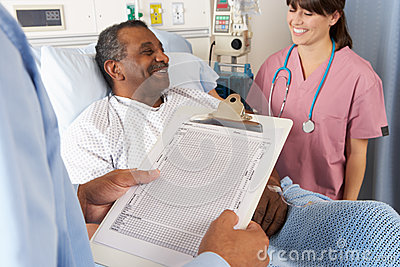 Doctor Looking At Chart With Senior Male Patient
