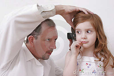 Doctor looking in little girl s ear