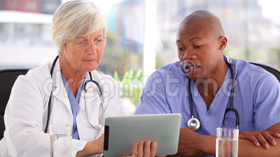 Doctor maduro que habla con una enfermera delante de una pantalla táctil almacen de metraje de vídeo