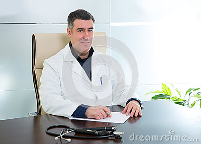 Doctor man sitting in hospital office desk portrait