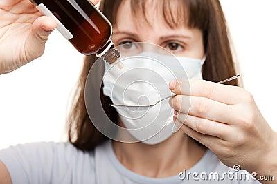 Doctor in mask holding medicine syrup