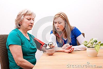 Doctor measures senior adult the blood pressure