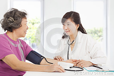 Doctor measuring blood pressure of senior woman