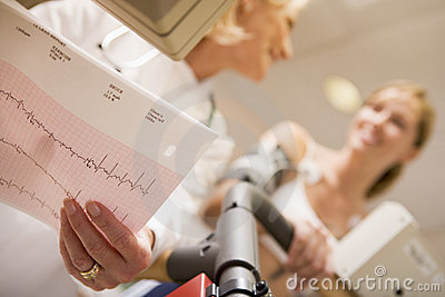 Doctor Monitoring Female Patient On Treadmill