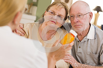 Doctor or Nurse Explaining Prescription Medicine to Senior Coupl