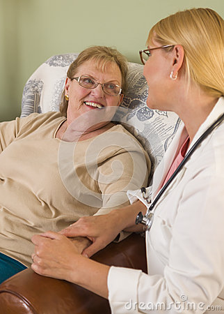 Doctor or Nurse Talking to Sitting Senior Woman