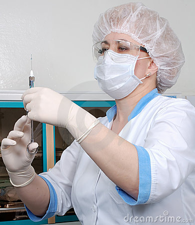 Doctor or nurse in uniform preparing a syringe