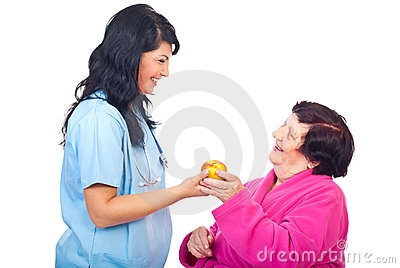 Doctor offering apple to a elderly patient
