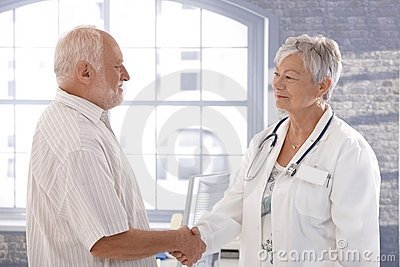 Doctor and patient shaking hands smiling
