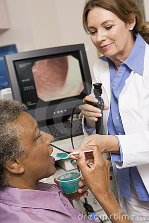 Doctor Performing Laryngoscopy On Patient
