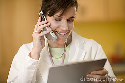 Doctor on phone reading medical records
