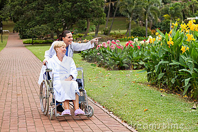 Doctor pushing wheelchair patient in park