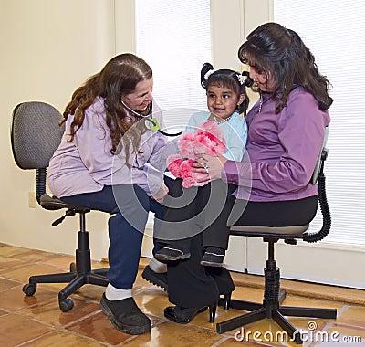 Doctor que examina a una pequeña muchacha del nativo americano