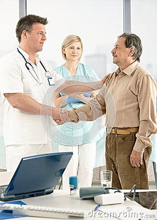 Doctor que felicita al paciente mayor en la recuperación