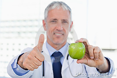 Doctor showing an apple with the thumb up