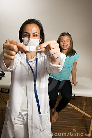 Doctor showing a band-aid while little girl happil