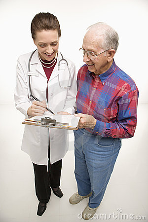 Doctor showing papers to elderly man.